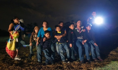 Central American children in a group looking scared at night next to an immigration officer with a flashlight.