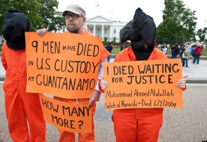 "Protresters demanding the closing of the Guantanamo detention facility and the end of the ongoing hunger strike by 103 of the inmates stand outside the White House in Washington on May 24, 2013. US President Barack Obama Thursday laid out new guidelines for drone strikes abroad and launched a new bid to close the Guantanamo Bay prison, seeking to rein in a ""boundless"" US war on terror.    AFP PHOTO/Nicholas KAMM        (Photo credit should read NICHOLAS KAMM/AFP/Getty Images)"