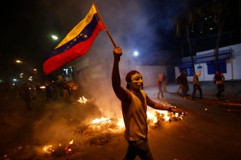 An opposition demonstrators holds a Venezuelan flag in front of a burning barricade during a protest against President Nicolas Maduro's government in Caracas February 15, 2014. Protesters gathered to demand the president's resignation, denouncing him over grievances ranging from political repression to daily issues such as inflation, shortages of basic products, and rampant crime.