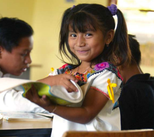 This picture shows a happy little girl getting an education. NGOs and other services try to provide education for street children to help them get out of the life situation the street has provided.