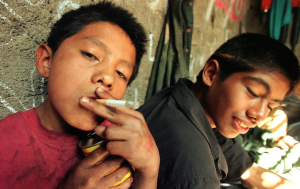 In this picture  we see children get a fix off of sniff thinner in a sewer in Mexico City. Children often start using  sniffer thinner to numb hunger but it becomes an addiction for many.   Photo Copyright Heriberto Rodriguez