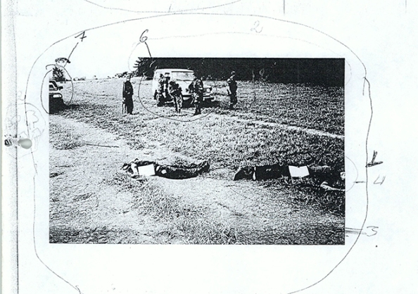 Photocopy of a photograph of soldiers standing behind the bodies of two alleged victims from 2004.  The photograph came from the Attorney General's office and has markings drawn by one of the witnesses.