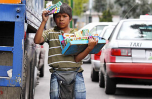 In this picture we see a boy selling chewing gum in the streets of Mexico City. Often children do not go to school in order to make money. As shown in this picture children are risking their lives by doing jobs like these.  Apart from risking their lives they are not getting an education and missing school to do this work.