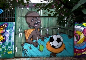 A graffiti painted by Brazilian street artist Paulo Ito on the entrance of a public schoolhouse in Sao Paulo, Brazil on May 23, 2014. A picture of the graffiti depicting a starving child with nothing to eat but a football has been shared more than 50,000 times on Facebook. AFP PHOTO / Nelson ALMEIDA