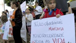 A young girl holds a sign reading in Spanish, 'You'll forget it, me, I will remember it for the rest of my life,' at a demonstration in front of the attorney general's office in Paraguay on Monday. About 200 people protested the high numbers of sexual abuse cases that have come to light in recent weeks as the country debates what should be done about a pregnant 10-year-old girl who was raped. (THE ASSOCIATED PRESS)